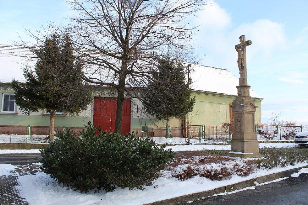 Hostějov se sněhovou pokrývkou. Kříž na návsi.