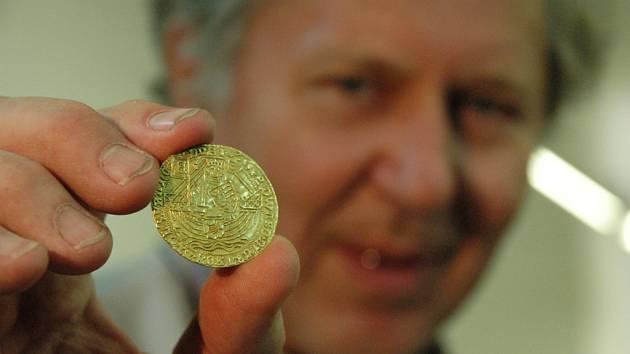 Jan Šmerda ukazuje jednu z mincí, které jsou součástí zlatého pokladu.
