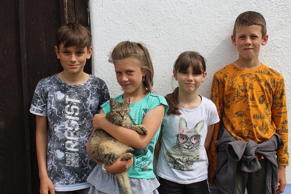 Pět památkových domků v hlucké ulici Rajčovňa. Děti s kočkou u vrat.