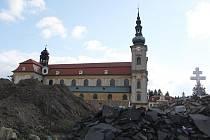 Hromady hlíny, betonu a vysloužilých materiálů čekají před bazilikou na zpracování.