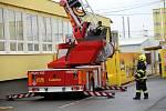 Hasičské cvičení: evakuace osob ze střechy budovy Hamé pomocí požární plošiny v Uherském Hradišti