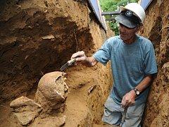 Ján Leško, dlouholetý pomocník archeologa Luďka Galušky, opatrně odkrývá obě kostry ležící nad sebou.