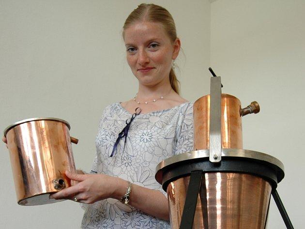 Marta Kondrová představuje repliku stolního destilačního zařízení.