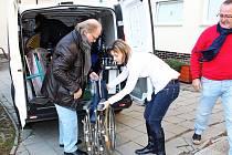 Pracovnice domova Veronika Novotná přebírá od Horsta von Brechana vozíček pro handicapované klienty.