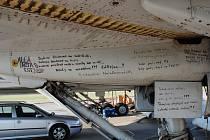 Letečtí nadšenci se při demontáži Tupolevů na pražském vojenském letišti povzbuzují motivačními nápisy.