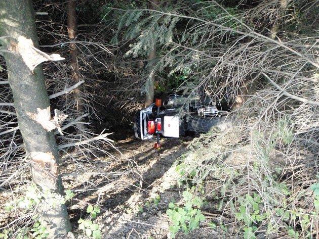 Motorkář i se svým strojem skončil po nehodě v hustém lesním porostu.