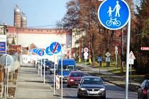 19 dopravních značek které postupně určují stezku pro cyklisty a pěší a vzápětí ji ruší.