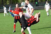Hodonínský obránce Jiří Maršálek (v červeno-černém) nechtěně nastřelil balonem hráče Uherského Brodu.