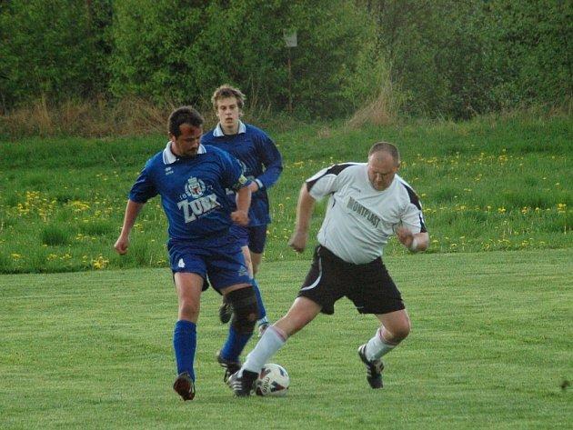Přetahovaná o body mezi fotbalisty Nezdenic a Polešovic (v tmavém) nakonec skončila nerozhodně. Blíže k vítězství měli domácí, hosté ale v nastaveném čase vyrovnali na konečných 2:2.