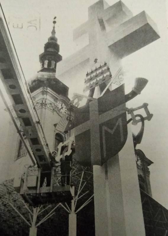 17 metrů vysoký dvouramenný cyrilometodějský kříž nese také papežský znak. Instalace v dubnu 1990.
