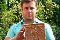 Komorový reliéfně zdobený kachel se symbolickým vyobrazením evangelisty Lukáše v podobě okřídlené sedící postavy s býčí hlavou