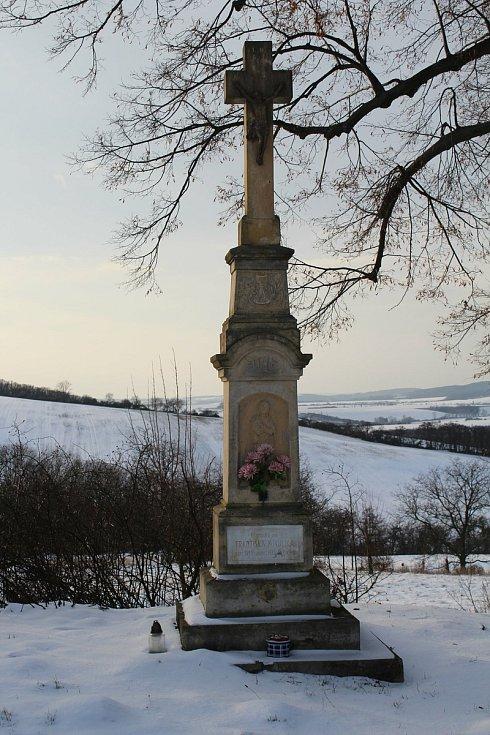 Hostějov se sněhovou pokrývkou. Kříž na konci obce.