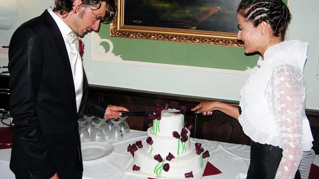 Novomanželé rozkrajují svatební dort.