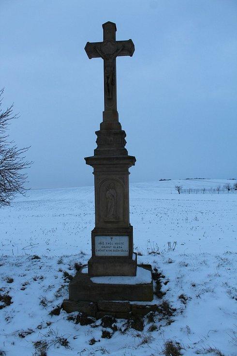 Hostějov se sněhovou pokrývkou. Kříž u příjezdu do vesnice.
