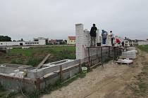 Zaměstnanci stavební firmy dokončují vnější výstavbu hřbitovní zdi v nové části staroměstského hřbitova.