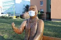 Recese v podobě ochranné roušky přes ústa dřevěné plastiky Jana Antonína Bati sedícího v Uherském Hradišti na lavičce u řeky Moravy.