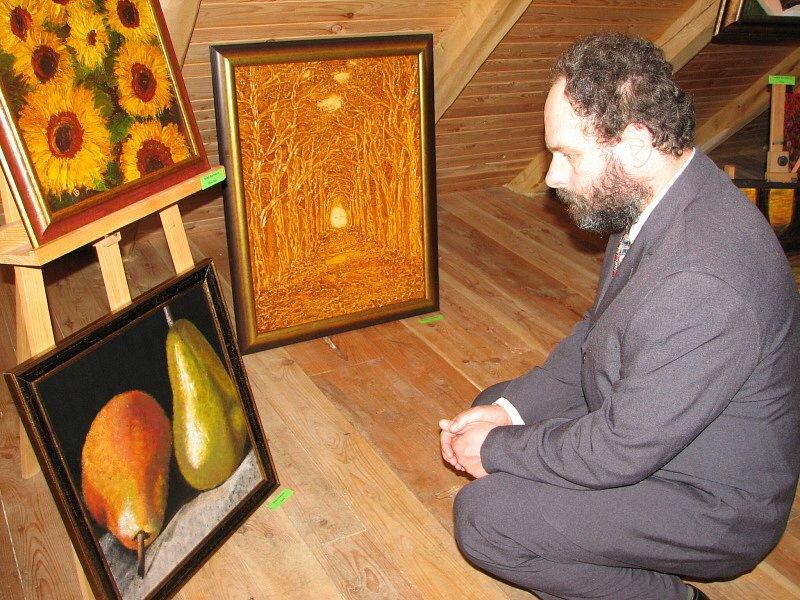 Nejeden z účastníků vernisáže se musel k obrazům hluboce sklonit nebo i dřepnout jako Jaroslav Lýsek na snímku.