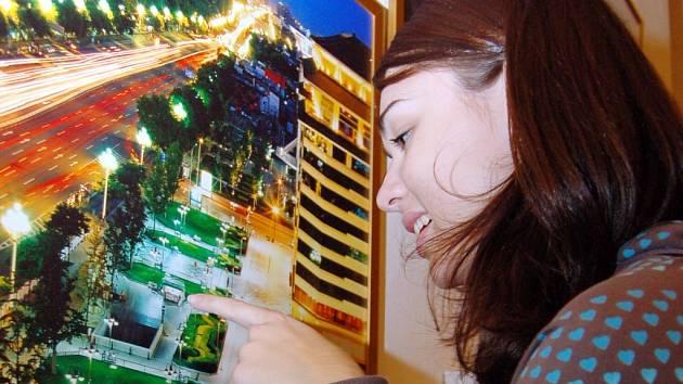 Jedna z návštěvnic výstavy obdivuje vystavené fotografie.