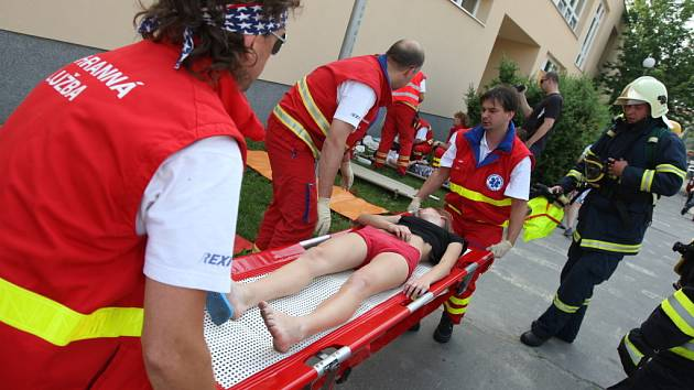 Hasiči z budovy vynášeli na nosítkách zraněné školáky. Těch se pak ujali zdravotníci, kteří je postupně ošetřovali.