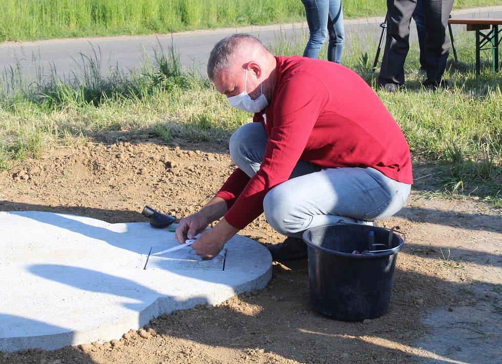Kameník ze Zlechova Petr Novák upravuje místo k uložení žulové dlaždice nad místem uložení schránky.