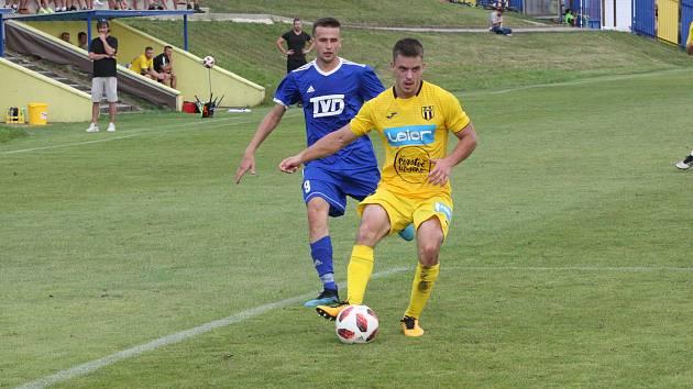 Fotbalista divizního Strání Robin Holík (ve žlutém dresu) stejně jako bratr Libor nastupuje na kraji obrany.