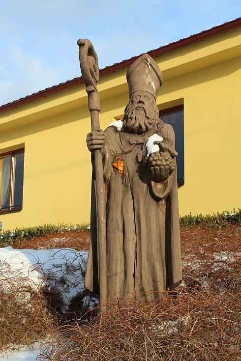 Hostějov se sněhovou pokrývkou. Dřevěná plastika sv. Urbana.