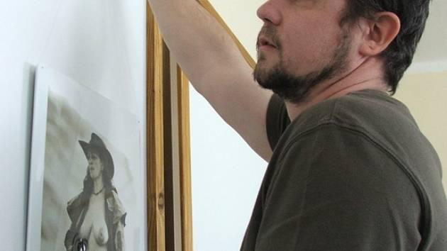 Jeden z autorů výstavy, Milan Zámečník při instalaci fotografií.