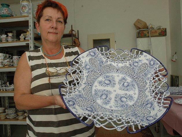 Irena Dosoudilová v keramické dílně v Tupesích. Ona sama maluje na výrobky krajky.