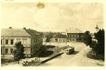Pohled na dnešní náměstí Svobody ve směru od severozápadu. V popředí hlavní silnice a křižovatka, vlevo budova školy postavená v roce 1886, v pozadí ční věž kostela sv. Petra a Pavla.