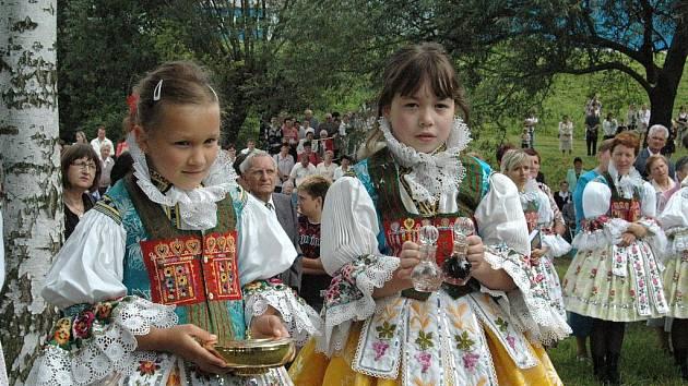 Děvčátka nesou obětní dary, zatímco početná skupina ministrantů se modlí hned vedle kapličky.