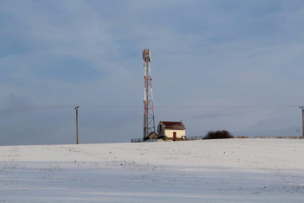 Hostějov se sněhovou pokrývkou. Radiotelekomunikační věž a vodojem.