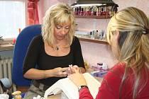 Daniela Süsserová, majitelka zlínského salonu Daniela, upravuje zákaznici ruce.