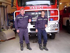 Velitel sboru dobrovolných hasičů Hluk Ivan Kotačka (vpravo) společně se svým kolegou před zásahovým vozem.
