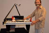 Stanislav Nemrava pózuje u jednoho ze svých děl.