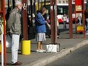 Lidé čekající na autobusové zastávce. Ilustrační foto.