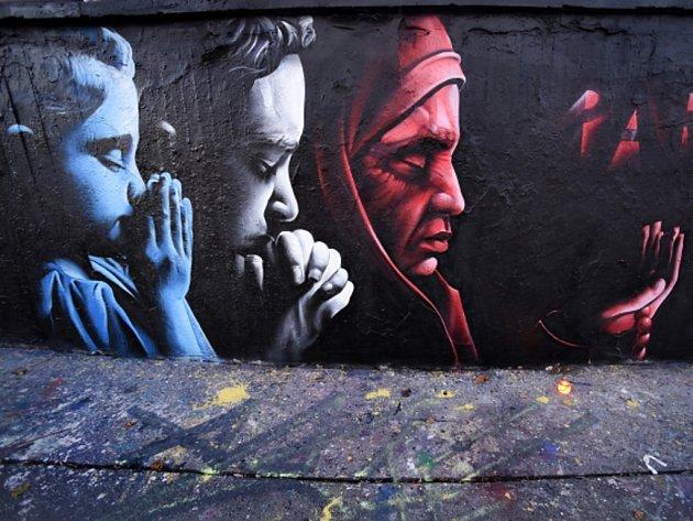 Graffiti na zdi určené pro legální tvorbu ukazuje tváře modlících se lidí v barvách francouzské vlajky. od umělce s přezdívkou ChemiS.