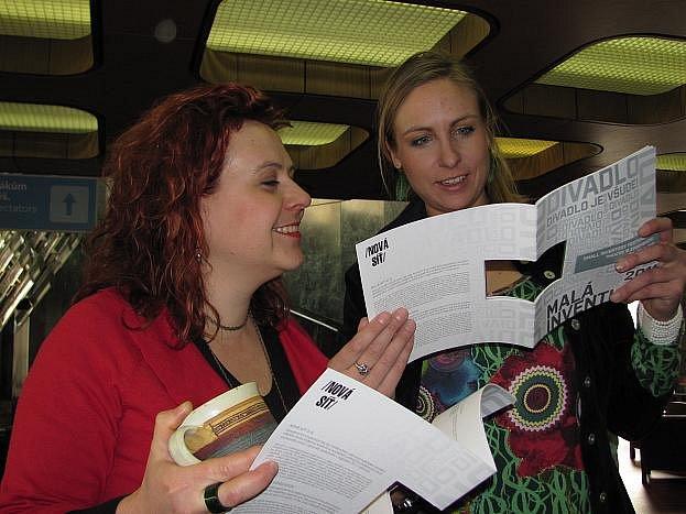 """Šárka Havlíčková (vlevo), organizátorka festivalu Malá inventura a Olga Cieslerová, tisková mluvčí festivalu, debatují nad netradičním katalogem,, v jehož středu je """"bílá"""" díra."""