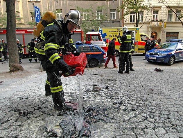 TRAGICKÁ NEHODA. Výsledkem pořáru karlínské trafostanice je těžce popálený pracovník Pražské energetiky. Hasič na snímku polévá vodou zbytky ohořelého oblečení zraněného muže.