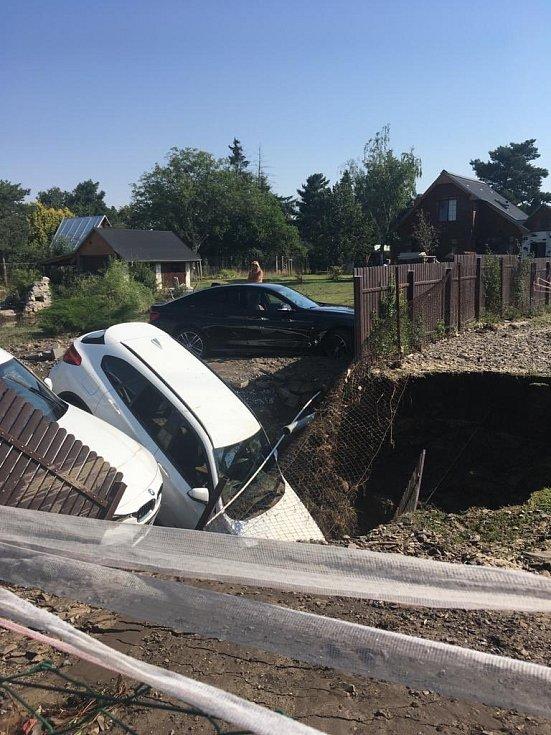 Do kaverny vzniklé únikem vody z prasklého vodovodního řadu, zapadly zaparkované automobily.