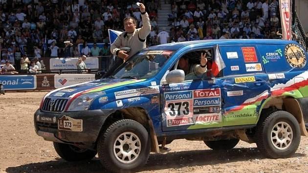 V cíli slavné rallye Dakar. Jiří Janeček se vyklání z vozu, za volantem je Viktor Chytka.