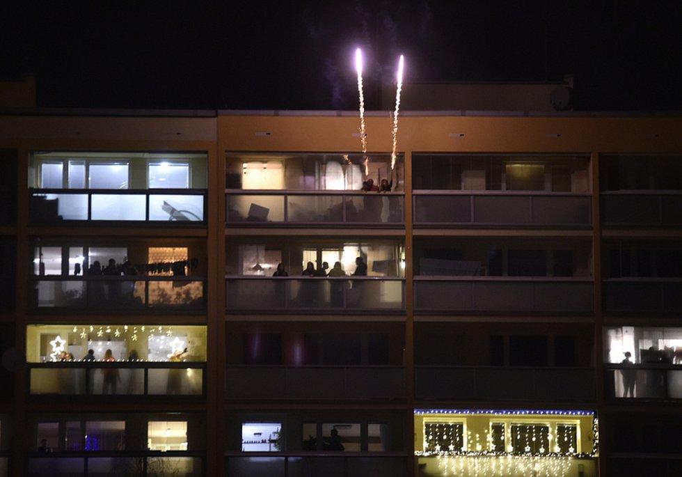 Lidé odpalovali rachejtle z balkonů při silvestrovských oslavách v noci na 1. ledna 2021 na sídlišti Jižní město v Praze.