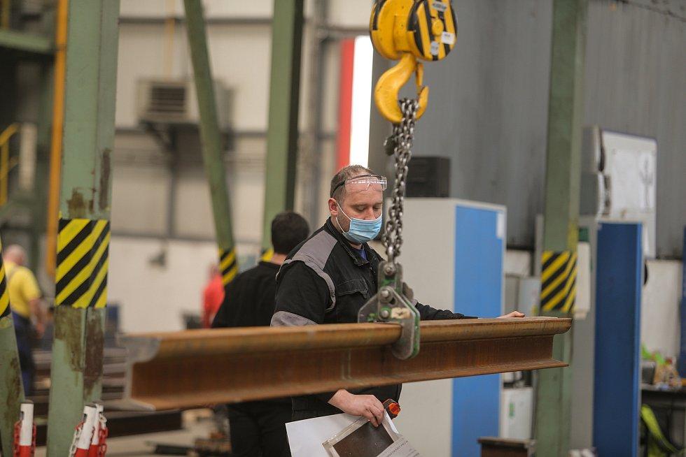 Pracovník strojírny přemisťuje kolejnici do ohýbačky kolejnic.