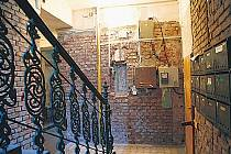 RUINA. Na první pohled vypadá dům v Křižíkově 93 téměř vybydleně. Fasáda osekaná na cihly, provizorní dveře, chybějící zvonky a vysklená okna. Jenže uvnitř bydlí 13 domácností.