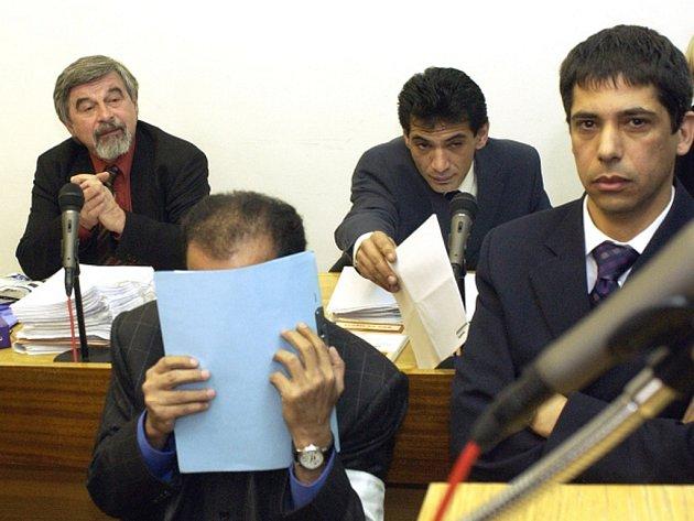 Listem papíru kryje svoji tvář člen katarské královské rodiny Hámid bin Abdal Sání při soudním přelíčení, které se konalo 25. dubna 2005.