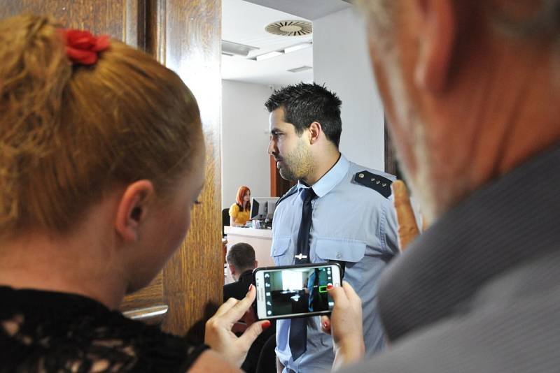 Desítky občanů s hesly v rukou přišly sledovat jednání přímo k soudu; před dveřmi jednací síně je ale na pokyn justiční stráže lidé museli odložit.