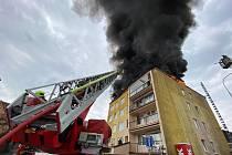 Střechu panelového domu V Praze 4 zachvátil požár.