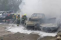 V areálu firem v Praze hořela hromada autovraků, hasiči je od sebe odtrhávali pomocí jeřábu.