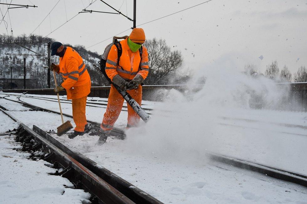 Sněhová kalamita způsobila 8. února 2021 komplikace ve veřejné dopravě. Na fotografii pracovní Správy železnic čistí koleje u nádraží Praha-Holešovice.