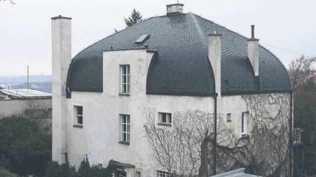 Břidlicová střecha, prolomená hranoly vysokých komínů dělá z vily na pohled zajímavou stavbu.