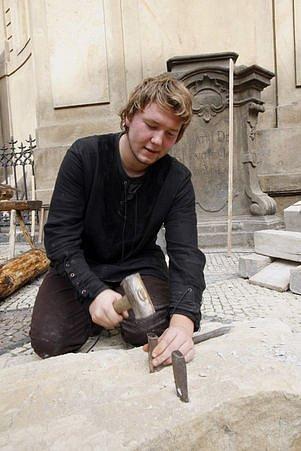 Kameník předvádí tehdejší techniku práce.